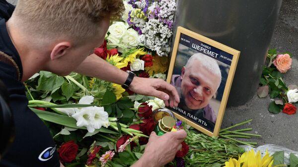Цветы и свечи на месте гибели журналиста Павла Шеремета в Киеве