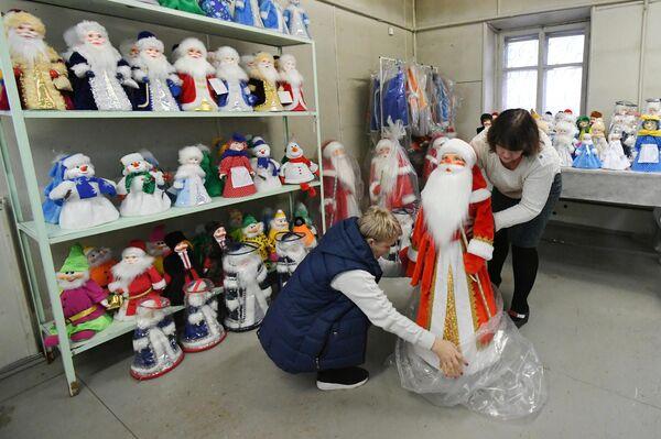 Сотрудницы упаковывают готовую куклу Деда Мороза, на фабрике Бирюсинка в Красноярске