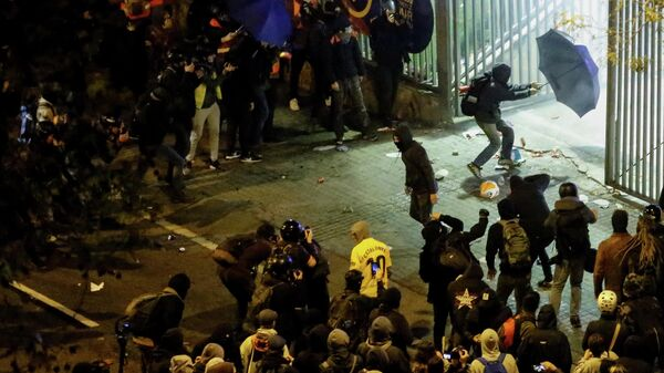 A protester with an umbrella tries to enter the Camp Nou stadium during a protest called by Catalan separatist movement Democratic Tsunami outside the stadium in Barcelona on December 18, 2019, during the El Clasico Spanish League football match between Barcelona FC and Real Madrid CF. - Twelve people were injured as police charged hundreds of masked protesters who set garbage bins on fire near Barcelona's Camp Nou stadium, as Barcelona and Real Madrid faced off in the first Clasico of the season, according to emergency services. (Photo by Pau Barrena / AFP)