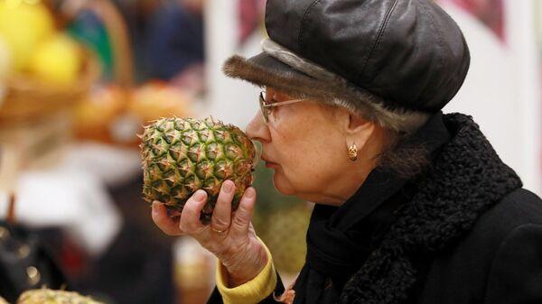 Женщина выбирает ананас