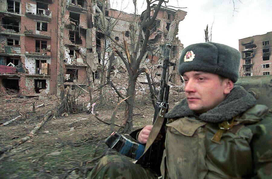 Российский солдат патрулирует районы Грозного, захваченные федеральными войсками 29 января 2000 года
