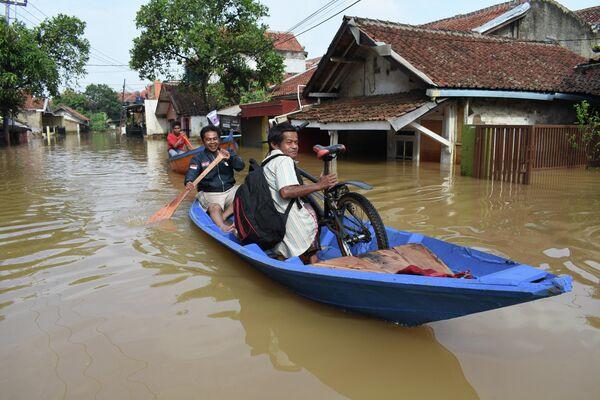Жители добираются на лодке через затопленную дорогу в Дайехколоте, Индонезия