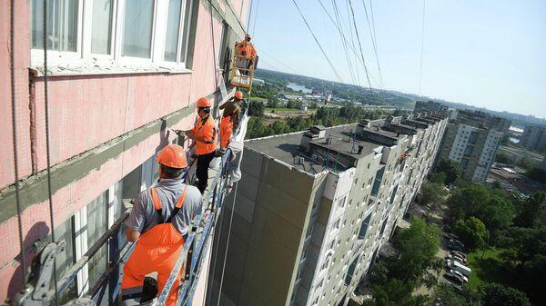 Рабочие проводят ремонт жилого дома