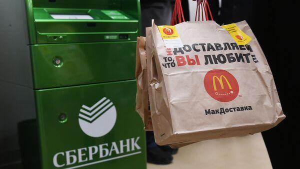 Посетитель совместного отделения Сбербанка и McDonalds в Москве стоит у банкомата с пакетами Макдоставки