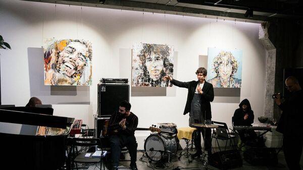 Игнат Кравцов на фоне своих работ в галерее Who I Am на выставке Faces