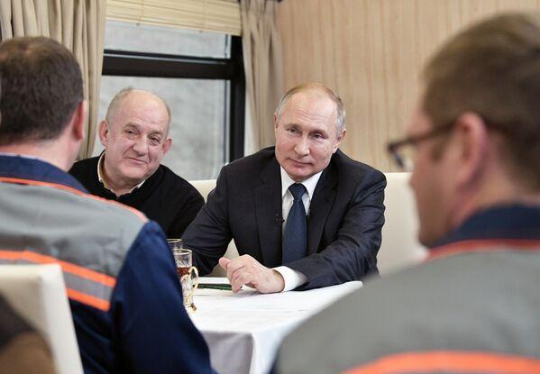 Президент РФ Владимир Путин общается с рабочими-мостовиками во время поездки на рельсовом автобусе, который отправился по железной дороге Крымского моста из Керчи в Тамань
