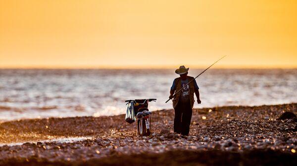 Рыбак на закате на набережной недалеко от Олимпийского Парка в Сочи