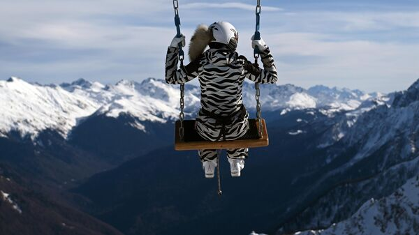 Туристка катается на аттракционе Качели над облаками на горнолыжном курорте Роза Хутор в Сочи