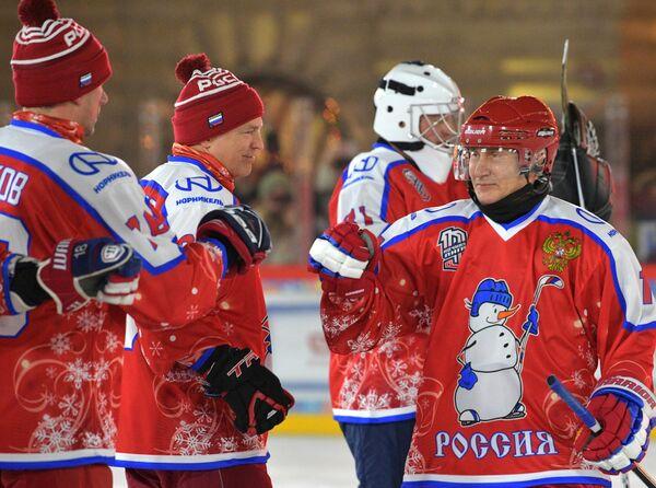 Президент РФ Владимир Путин приветствует игроков перед началом предновогоднего товарищеского матча Ночной хоккейной лиги на катке на Красной площади