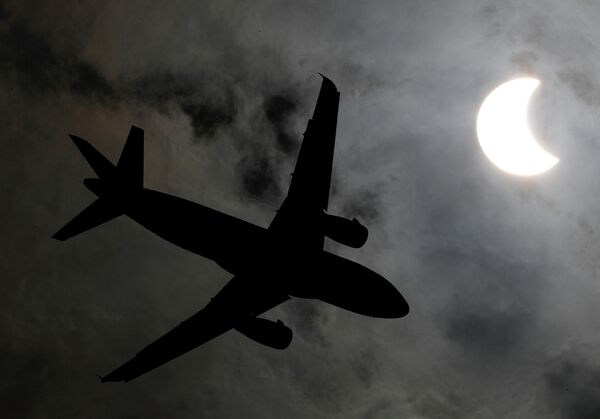 Самолет летит во время солнечного затмения в Бангкоке, Таиланд