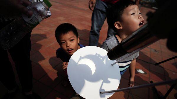 Дети наблюдают частичное солнечное затмение в Научном Центре образования в Бангкоке, Таиланд