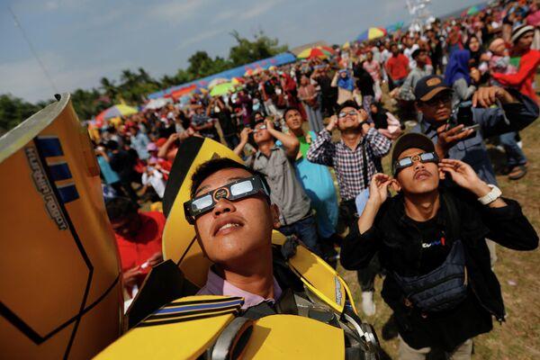 Люди наблюдают кольцевое солнечное затмение в Сиаке, провинция Риау, Индонезия