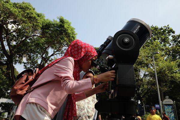 Девушка смотрит частичное солнечное затмение через телескоп в планетарии в Куала-Лумпуре, Малайзия