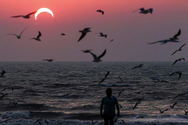 Мужчина на пляже в Кувейте во время частичного солнечного затмения
