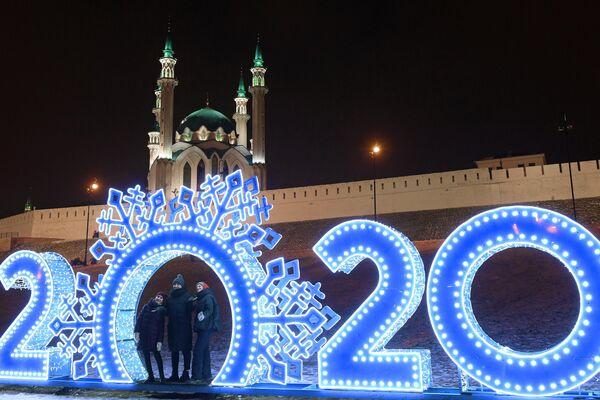 Прохожие фотографируются у новогодней иллюминации на фоне Мечети Кул-Шариф в Казани