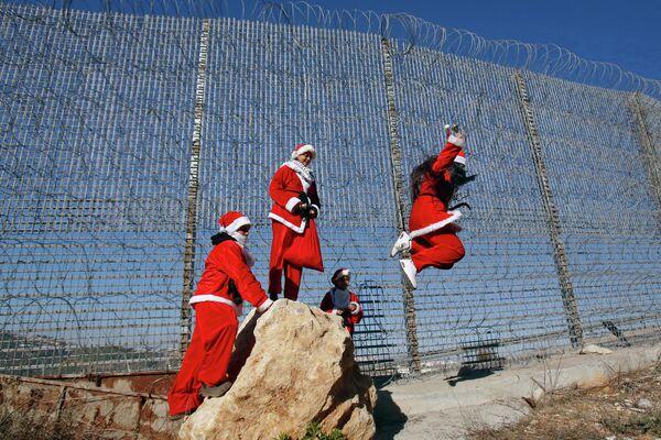 Палестинцы в рождественских костюмах прыгают с камня неподалеку от библейского города Вифлиема