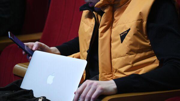 Журналист в жилете с логотипом агентства Sputnik