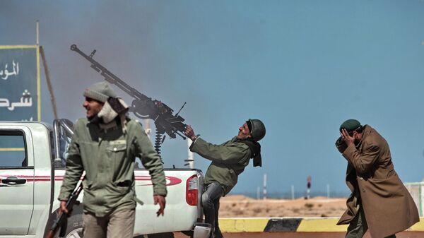 Боец оппозиции стреляет из пулемета в истребитель в городе Рас-Лануф в Ливии