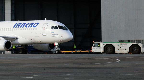 Тягач буксирует пассажирский самолет Сухой Суперджет-100 авиакомпании ИрАэро