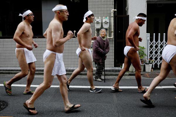 Женщина смотрит на мужчин бегающих вокруг храма Teppozu Inari во время церемонии в Токио, Япония. 12 января 2020 года