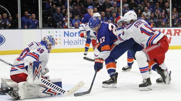 Игрок ХК Нью-Йорк Рейнджерс Александр Георгиев (18) и игрок ХК Нью-Йорк Айлендерс Андерс Ли (27) в матче регулярного чемпионата Национальной хоккейной лиги (НХЛ)