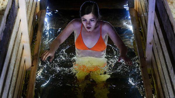 Девушка во время крещенских купаний в Строгинской пойме в Москве