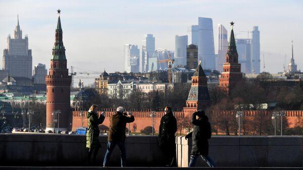 Прохожие фотографируются на Большом Москворецком мосту в Москве