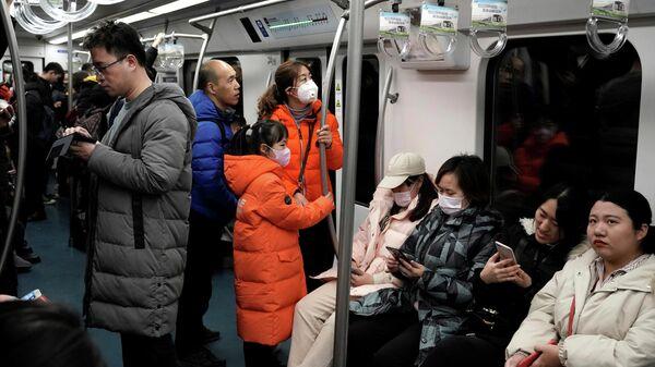 Люди носят маски во время поездки в метро в Пекине, Китай. 21 января 2020