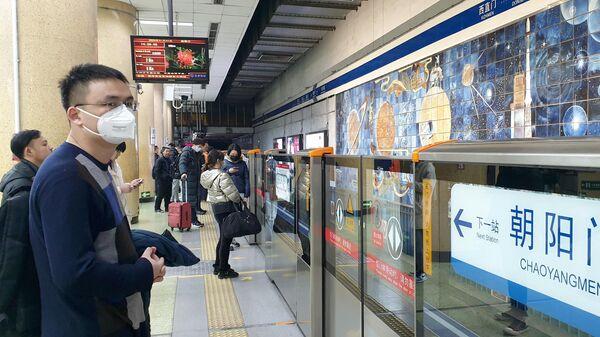 Пассажиры в защитных масках на одной из станций метро в Пекине
