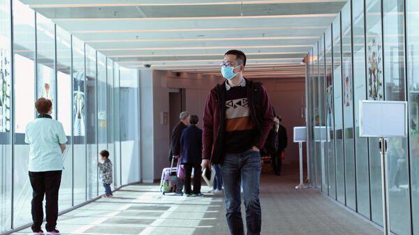 Пассажир в маске, прибывший из китайского Ханчжоу, в аэропорту Чанги, Сингапур