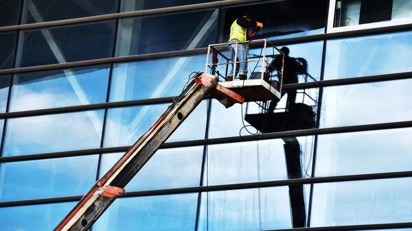 Рабочий моет окна многофункционального выставочного центра Минводыэкспо.
