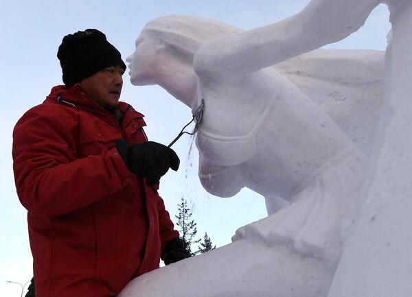 Победитель в номинации Снег, член команды HIT 1 работает над снежной скульптурой Сёрфинг на фестивале Волшебный лед Сибири в Красноярске