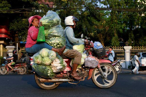 Местные жители перевозят овощи в городе Пном Пен, Камбоджа
