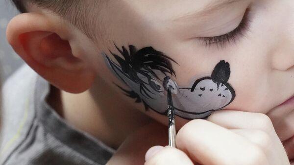 Мальчику рисуют на лице Волка на фестивале киностудии Союзмультфильм в Москве