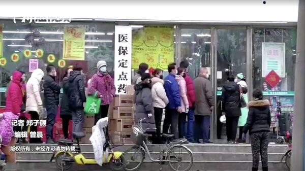 Люди в масках стоят в очереди в магазин в Ухане