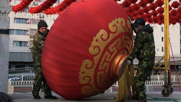 Рабочие демонтируют декорации для празднования Нового года по лунному календарю в Пекине, КНР
