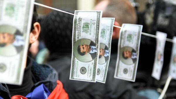Участники акции протеста оппозиции повесили денежные купюры с изображением председателя и основателя правящей в Грузии партии Грузинская мечта Бидзина Иванишвили перед зданием парламента в Тбилиси