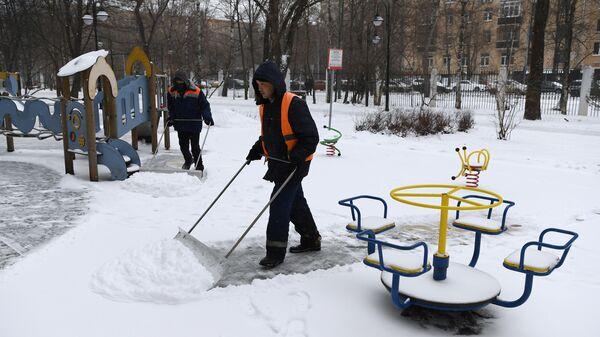 Сотрудники коммунальной службы чистят детскую площадку от снега в Москве