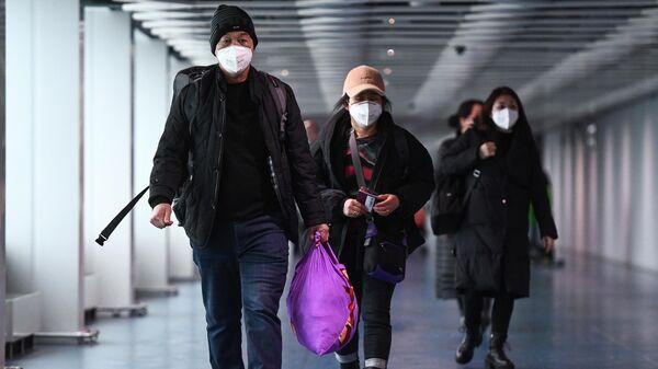Пассажиры, прибывшие из Китая, в аэропорту