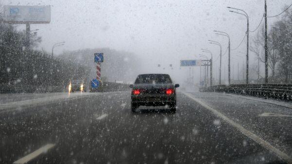 Автомобиль едет по Минскому шоссе во время снегопада в Москве