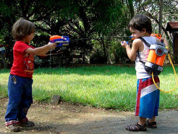 Дети играют с водяными пистолетами