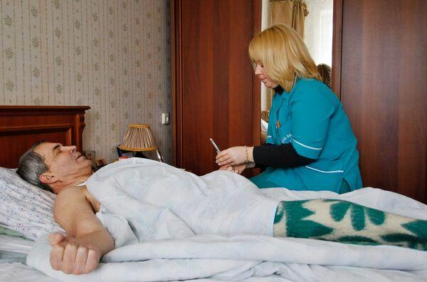 Бригада скорой медицинской помощи осматривает больного. Архив