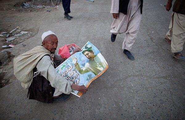Мужчина держит в руках постер с изображением Абдулы Абдулы, кандидата в президенты Афганистана