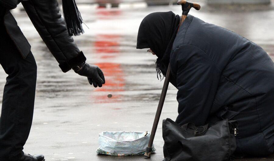 Женщина, просящая милостыню, на одной из улиц Москвы
