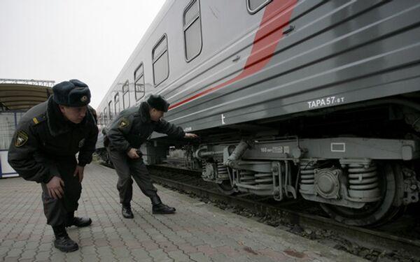 Наряд милиции осматривает вагоны поезда на железнодорожном вокзале