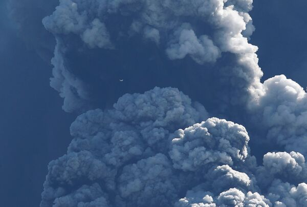 Самолет пролетает над местом извержения вулкана, расположенного на леднике Эйяфьятлайокудль
