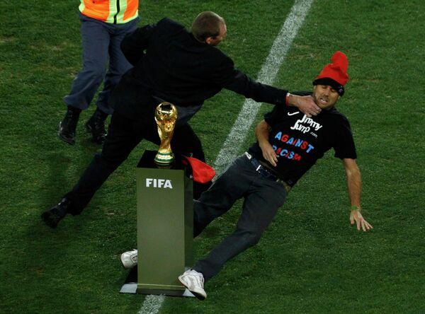 Охранник не дает болельщику дотронуться до Кубка Мира.