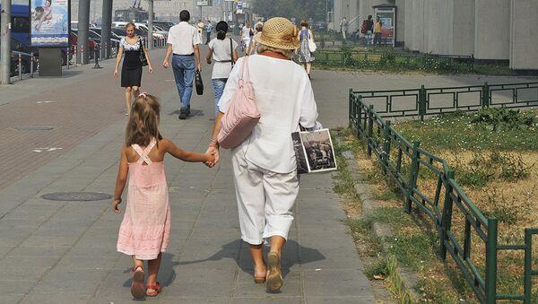 Бубушка с внучкой гуляет по городу. Архив