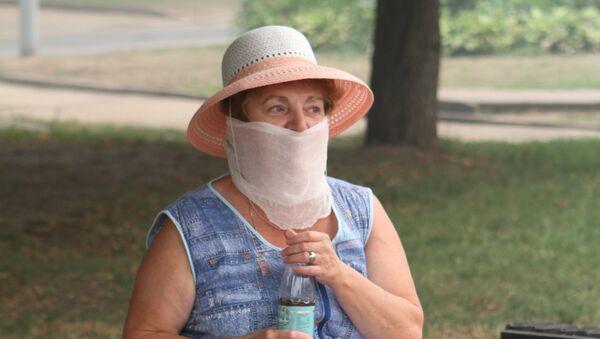 Женщина в защитной маске от смога. Архивное фото