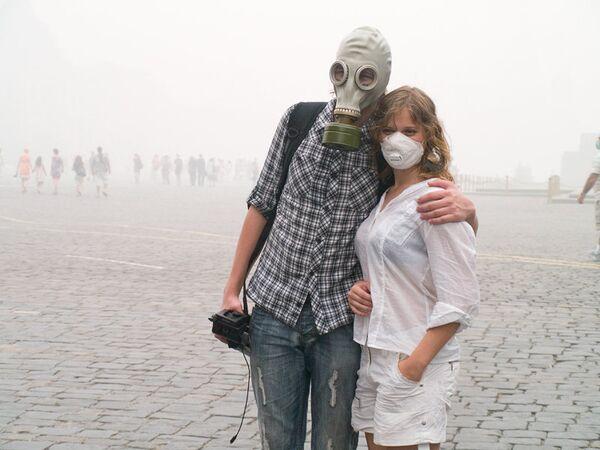 Люди в защитных масках в период смога в Москве. Архив